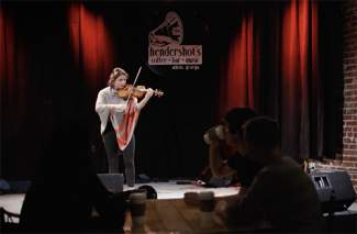 still photo of woman playing violin on a club stage