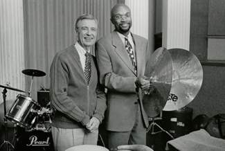 black and white photo of two men, with drums and cymbals