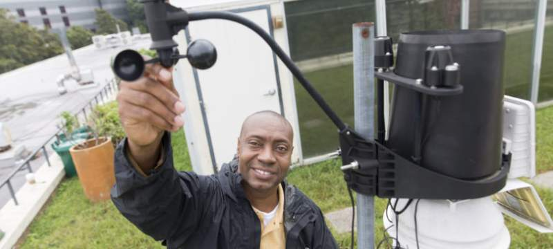 photo of man with wind gauge equipment, outside