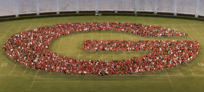 photo of people forming the letter G on a stadium grass field