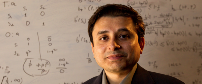 Environmental portrait of Creative Research Medal winner Prashant Doshi with mathematical equations on white board in background