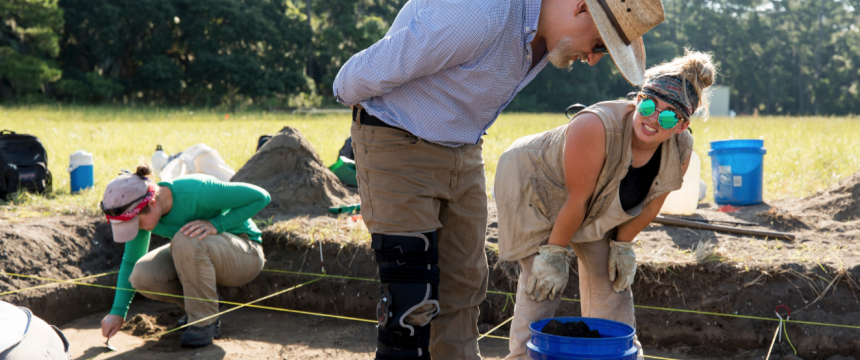 Professor Victor Thompson works with undergraduate student Katelyn Leka as they work on the excavation of their site.