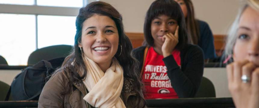 Three diverse female students grin as they listen to Daleah Goodwin's lecture in a women's studies class in the Miller Learning Center