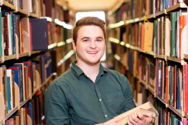 Environmental portrait of undergraduate Amazing Student Nicholas Twiner in the main library