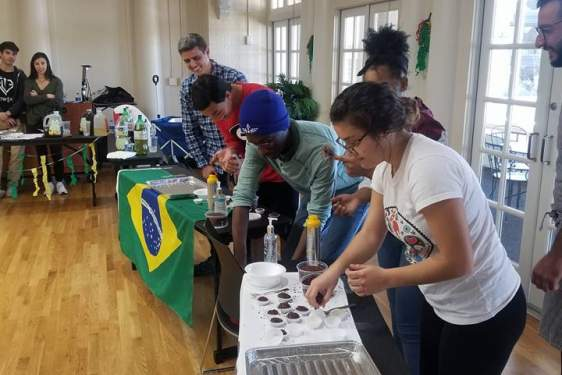 photo of students with table, flag and food