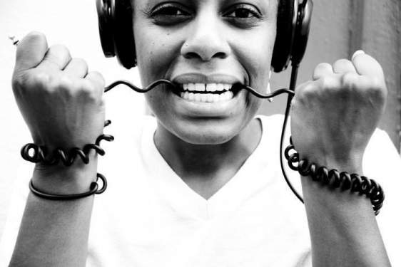black and white photo of woman wearing headphones with the cord in her teeth