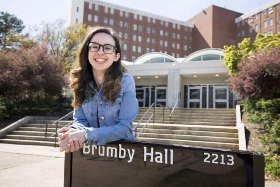 photo of woman leaning on dorm sign
