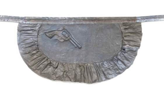 metal sculpture of apron with pistol