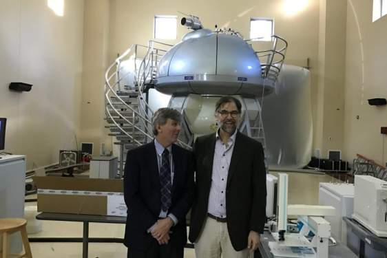 photo of men with NMR machine in background