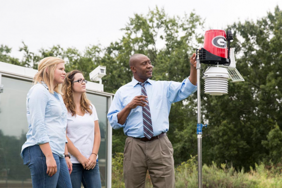 photo of man and two women with weather station