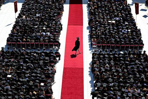 photo of student walking across red carpet at commencement