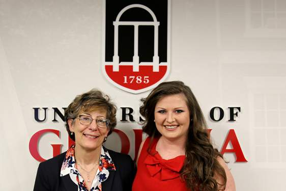 photo of two women standing in front of UGA logo