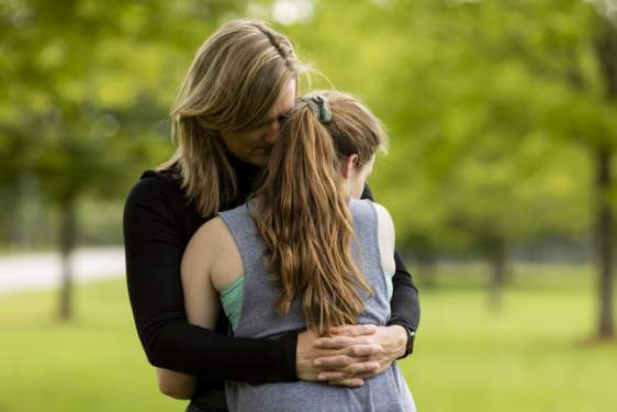 photo of woman and girl in embrace