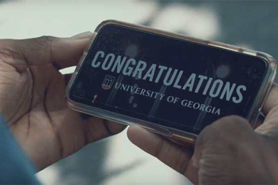 photo of hands holding a cell phone with congratulations