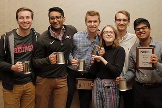 photo of six students holding award cups