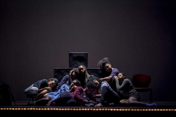photo of people sitting close together on a darkened stage