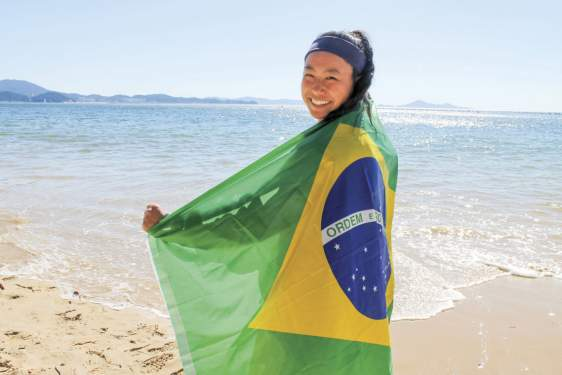 photo of woman on a beach with flag of Brazil