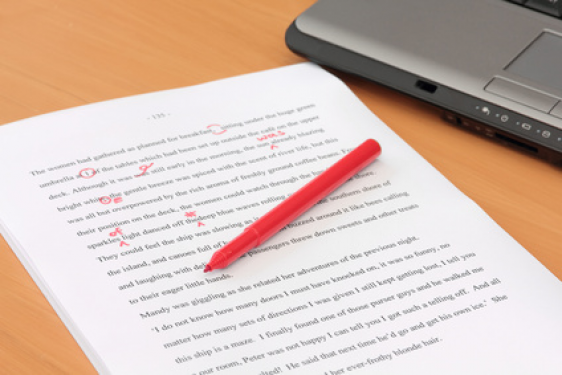 photo of paper with text, red pen, and laptop
