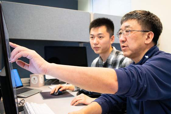 photo of two men at a computer screen